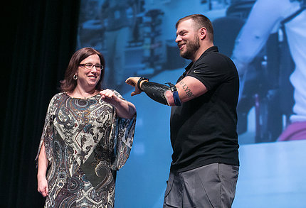 An audience volunteer helps Mills demonstrate features of his prosthetic arm.