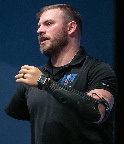 Mills raises his prosthetic arm