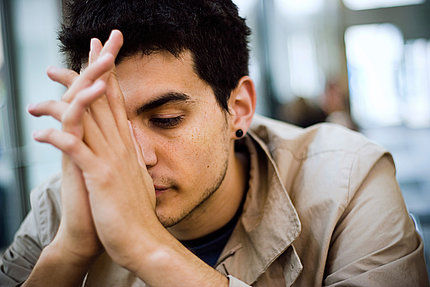 Young man with folded hands in front of his face.