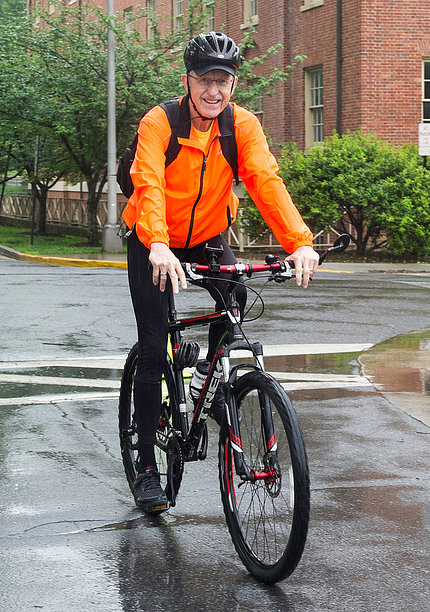 Dr. Francis Collins bicycles onto campus.
