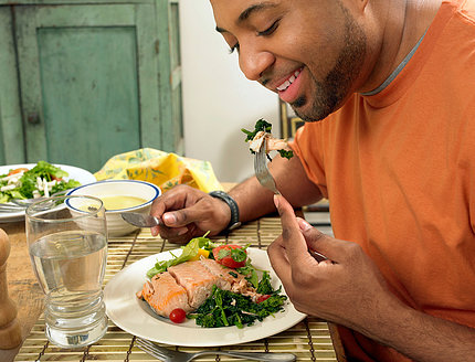A man sits at a table at home eating a salmon salad.