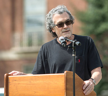 Pérez-Stable speaking at a podium outside.