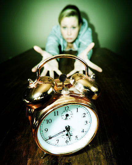 Young woman reaching out with both hands for alarm clock.