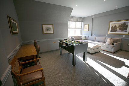 View of room with lounge chairs, sofa and Foosball table with sunlight coming through a corner window