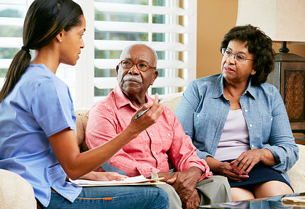 Nurse making notes during home visit with senior couple.