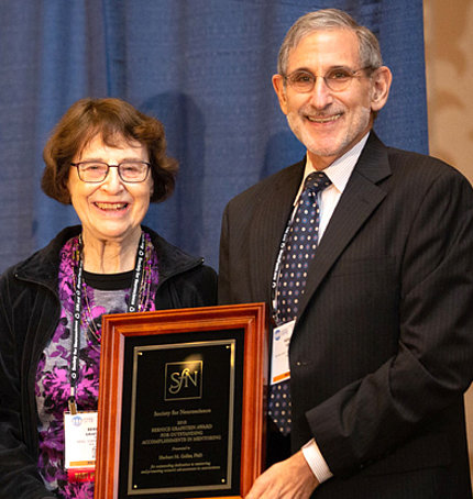 Dr. Geller receives a plaque from Dr. Grafstein