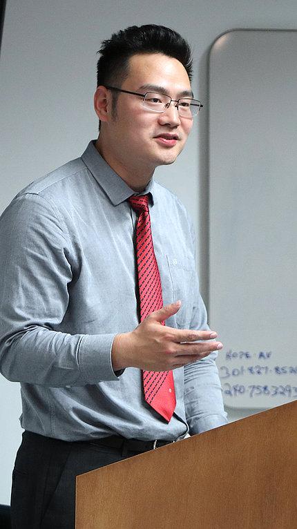 Dr. Jiang speaks at a podium
