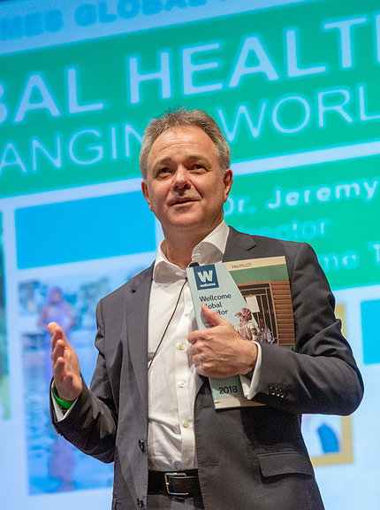 Farrar holds a copy of the first Wellcome Global Monitor report.
