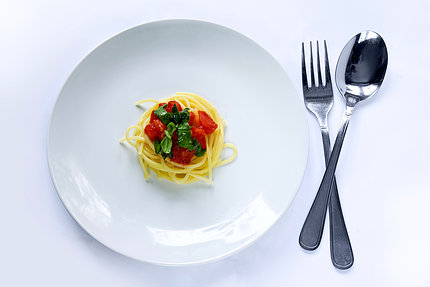 Spaghetti and red sauce on a white plate next to silverware