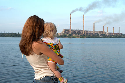 A mother and child look across a river towards a polluting power plant