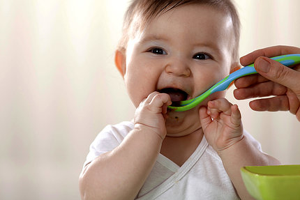 A baby eats a spoonful of food