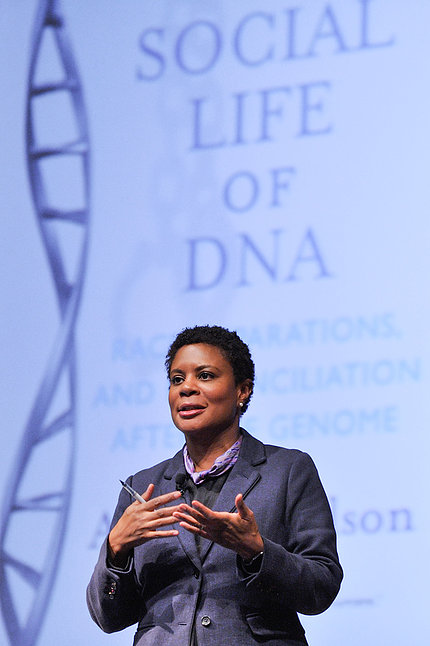 Dr. Alondra Nelson speaks in front of slide showing double helix that reads the social life of DNA
