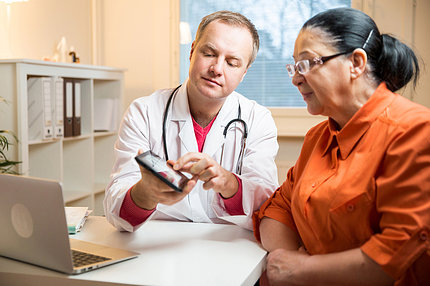 A doctor shows a female patient her test results on an a tablet screen.