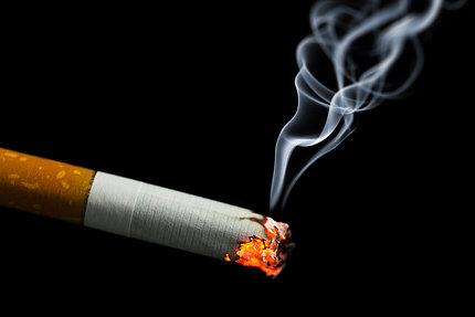 A burning cigarette on a black background