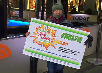 Anderson holds an NDAFW sign outside NBC's The Today Show studio in New York