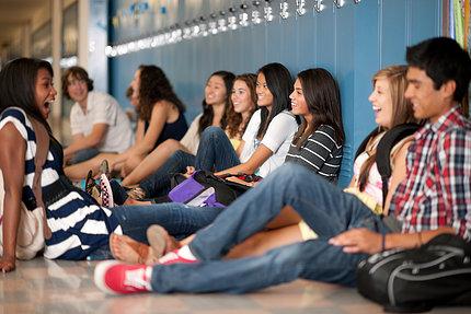 Teenagers sitting and talking on high school hallway floor.