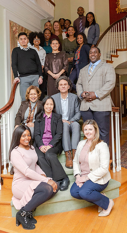 Group of iCURE scholars and staff pose with NCI leadership on a winding staircase.