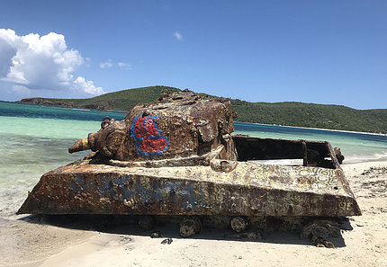 A rusty military tank sits on a beach in Puerto Rico