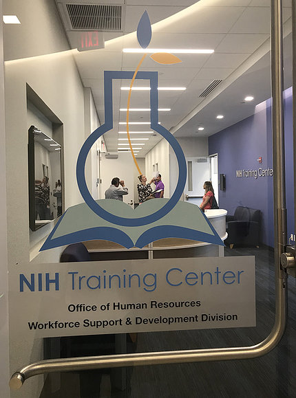 Through the glass door, staff gather in the lounge of the new NIH Trianing Center.