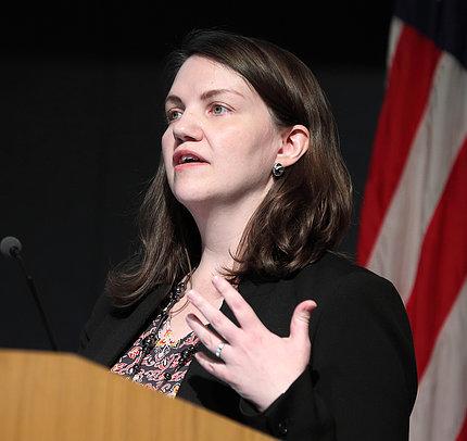 Dr. Sarah Runcie speaks at podium