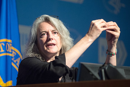 Kieffer gestures from podium during her lecture.