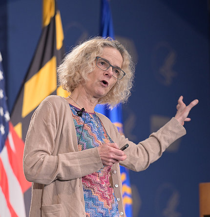 Dr. Nora Volkow talks from stage with outstretched arm