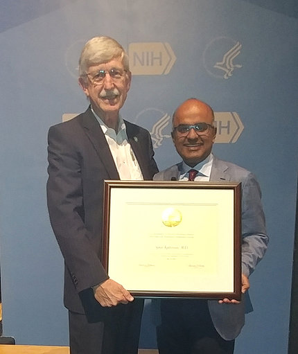 Dr. Kathiresan accepts plaque from Dr. Collins