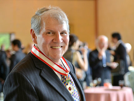 Katz wearing Rising Sun medal, with award reception in background