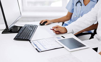 A doctor and a nurse look at a computer screen