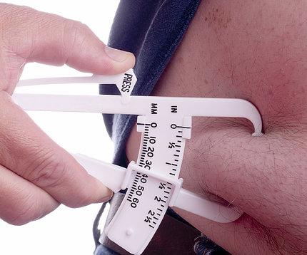A caliper pinches a person's belly fat.