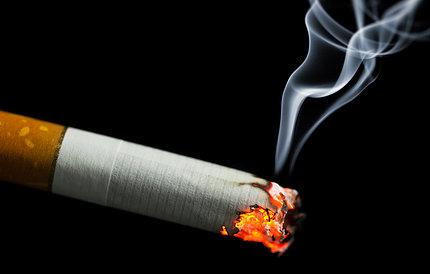 A lit cigarette burning on a black background.