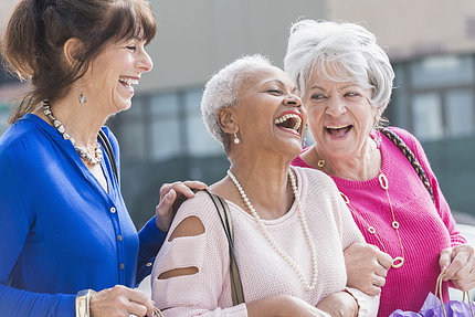 An older group of ladies share a laugh.