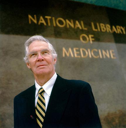 Dr. Lindberg stands in front of NLM.