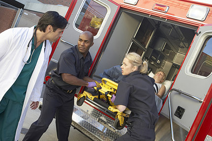 Two EMTs and one ER doctor take a patient out of an ambulance
