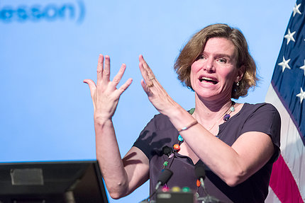 Mazzucato gestures with both hands from podium.