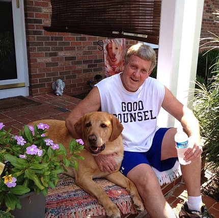 Moore sits on a stoop with his dog