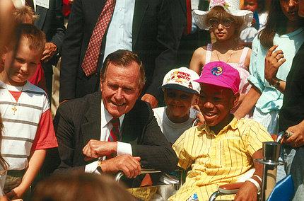 Bush kneels next a child