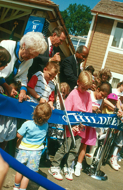 President Bush cuts a blue ribbon with giant scissors, while children look on