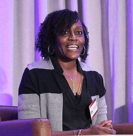 Numa speaks, seated on stage