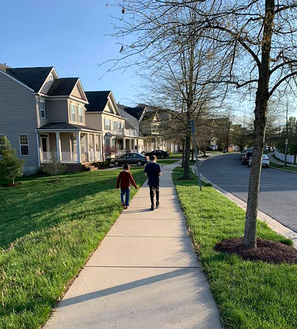 Seen from behind, 2 foster children walk together along the sidewalk.