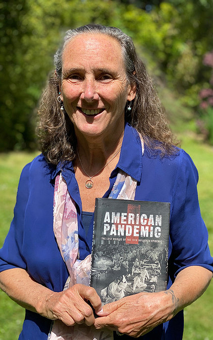 Dr. Bristow stands outside holding her book, titled, American Pandemic