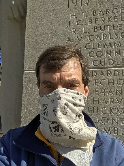 Professor Ewing, wearing a cloth mask, stands in front of pylon etched with names of World War I victims