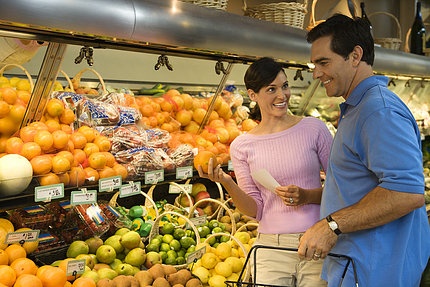 A man and woman shop for produce