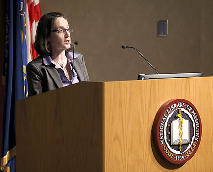 Schultheiss lectures from the NLM podium.