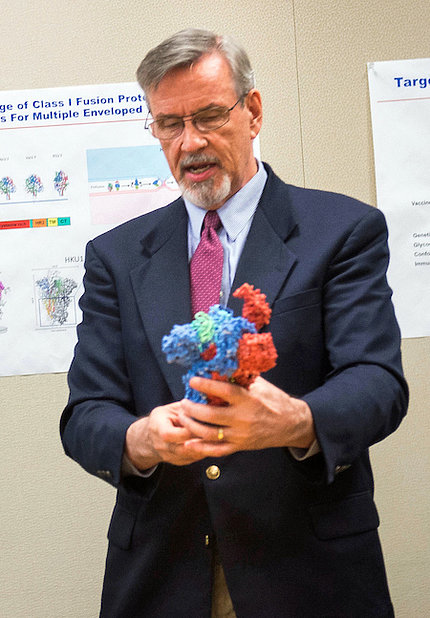 Dr. Graham holds up a 3D model of a flu virus