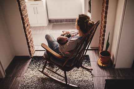 Woman and baby in rocking chair, facing window