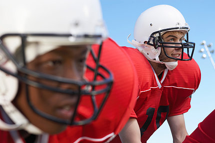 Close-up of two young men in football uniforms and helmets