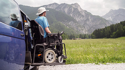 Man on wheelchair views mountains.