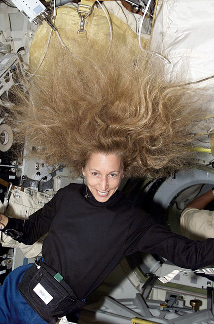 Ivins smiling with hair floating above her face, in zero gravity environment