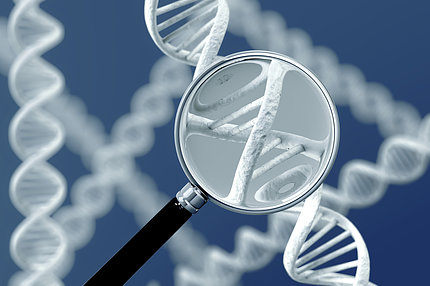 A magnifying glass enlarges twisty, double helix strands over a blue background.
